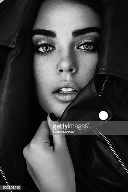 beautiful girl muffle in a leather jacket - black jacket stock pictures, royalty-free photos & images