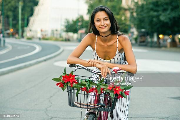 Beautiful girl on a bicycle looking at camera.