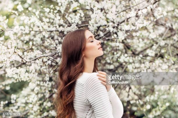 bella ragazza sullo sfondo del cespuglio primaverile - capelli foto e immagini stock