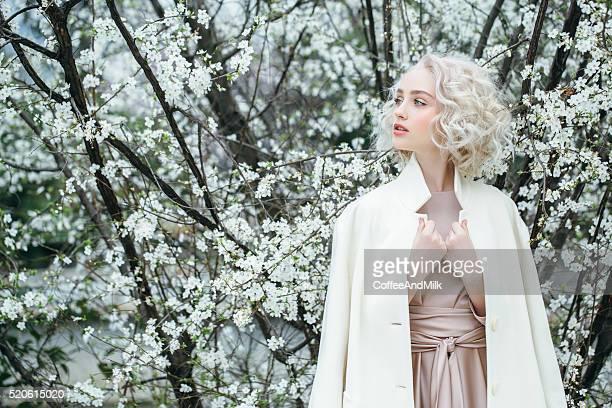 Schöne Mädchen auf dem Hintergrund der Frühling Busch