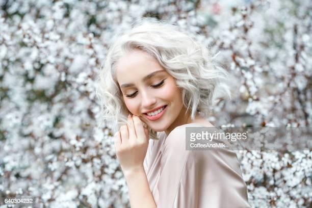 Hermosa chica en el fondo de primavera arbusto