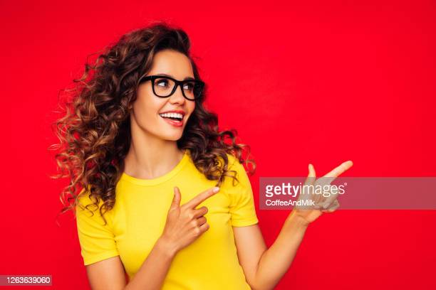 beautiful girl on the red background showing right direction with her fingers - eyeglasses stock pictures, royalty-free photos & images