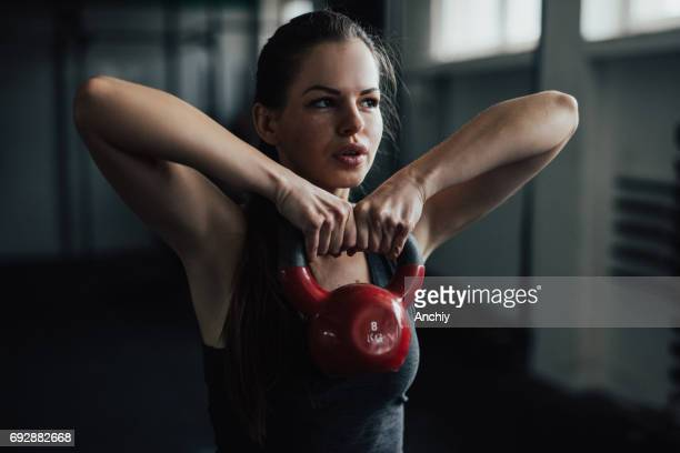 Beautiful girl performing exercise with kettlebell