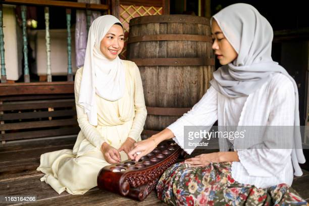 beautiful girl playing congkak and smiling - ibnjaafar stock photos and pictures