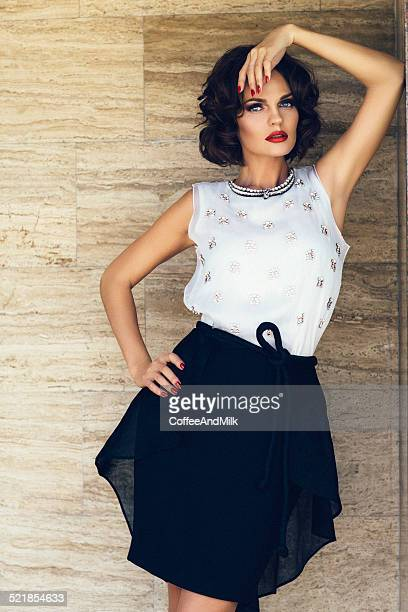 Beautiful girl posing on a background of the marble wall