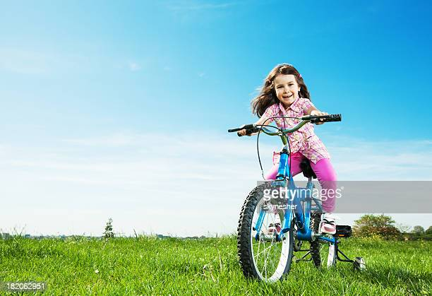 Beautiful girl riding a bicycle in park.