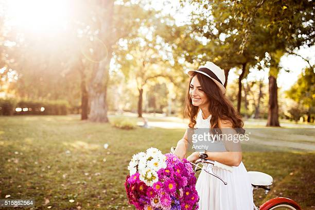 Schöne Mädchen auf ihrem Fahrrad mit Korb voller Blumen