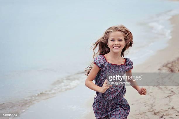 Beautiful girl (6-7) running on beach