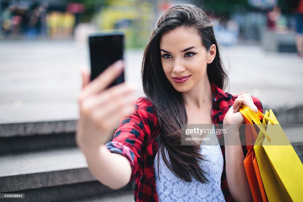 Beautiful girl shoping in the city and taking a selfie : Stock Photo