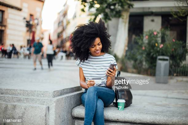 beautiful girl shopping online on the street - consumerism stock pictures, royalty-free photos & images