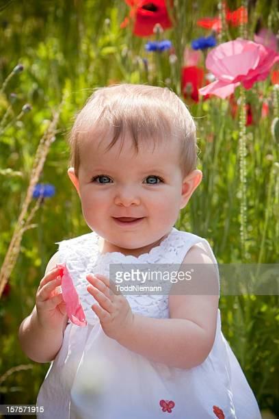 Beautiful girl sits in poppy field