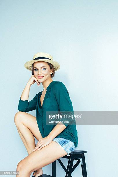 beautiful girl sitting at the studio - denim shorts stock pictures, royalty-free photos & images