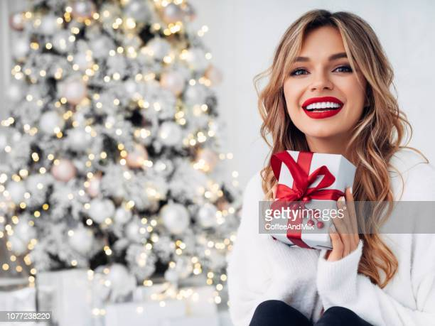 beautiful girl sitting in a cozy atmosphere near the christmas tree - red lipstick stock pictures, royalty-free photos & images