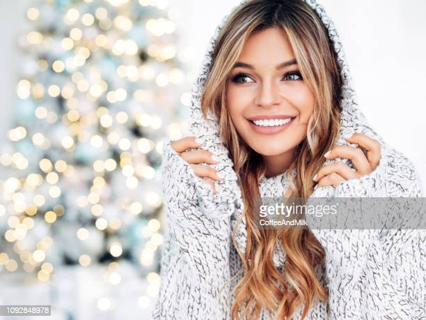 beautiful girl sitting near the christmas tree - hot female models stock pictures, royalty-free photos & images