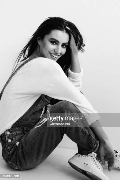 Hermosa Chica sentada en el suelo de la habitación tipo estudio