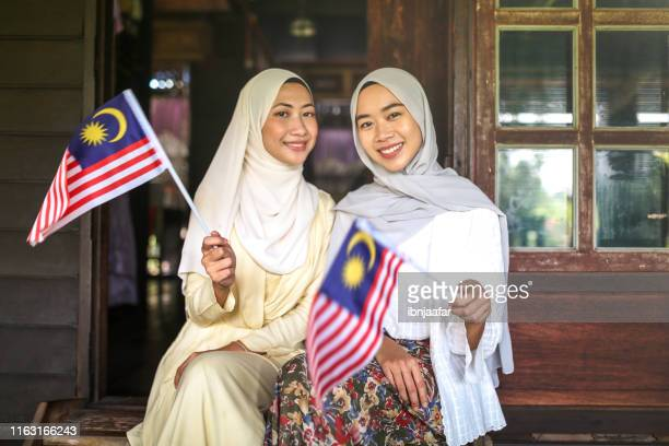 beautiful girl smiling and holding malaysia flag - ibnjaafar stock photos and pictures