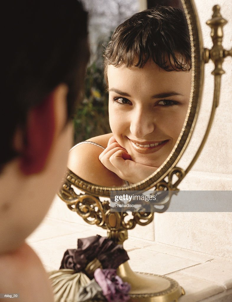 Beautiful girl smiling at reflection of a mirror stock photo getty beautiful girl smiling at reflection of a mirror stock photo voltagebd Gallery
