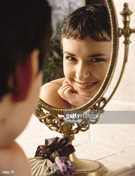 beautiful girl smiling at reflection of a mirror - 前髪 ストックフォトと画像
