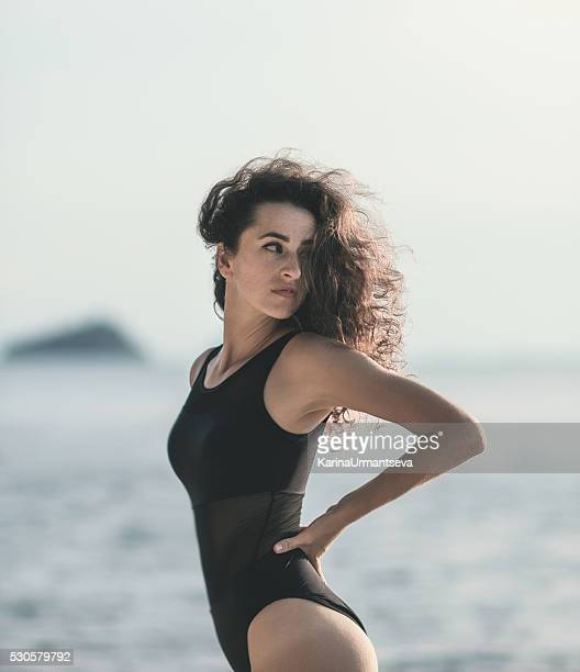 beautiful girl stands near the shore in summer