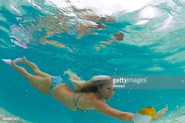 Beautiful girl swims with tropical fish