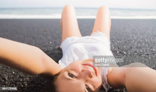 Beautiful girl taking a original selfie laying on the volcanic beach in the Lanzarote island smiling with the sea on the background during a travel vacation through the island. Millennial generation.