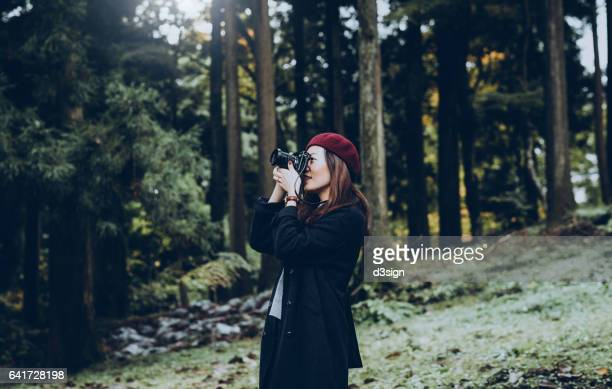 Beautiful girl taking photos in the woodland