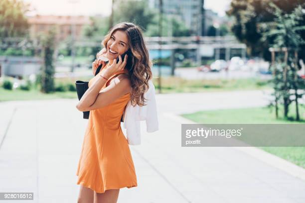 beautiful girl talking on the phone on the street - three quarter length stock pictures, royalty-free photos & images