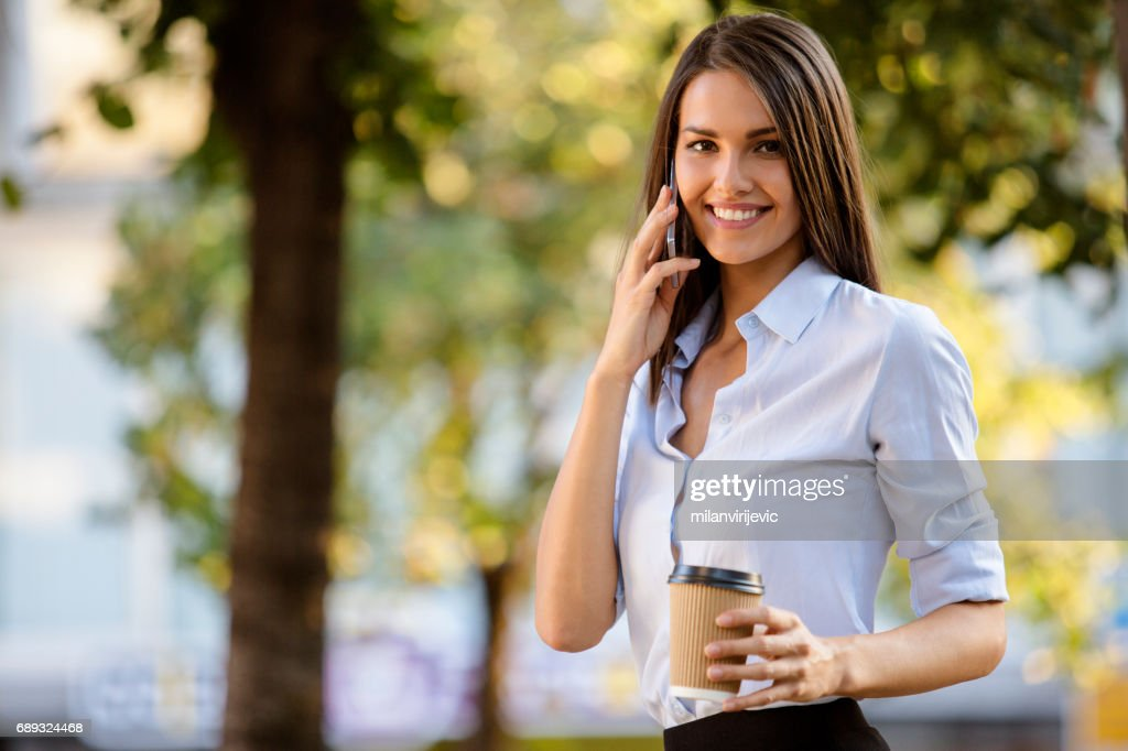 Beautiful girl talks on the phone holding cup of coffee : Stock Photo