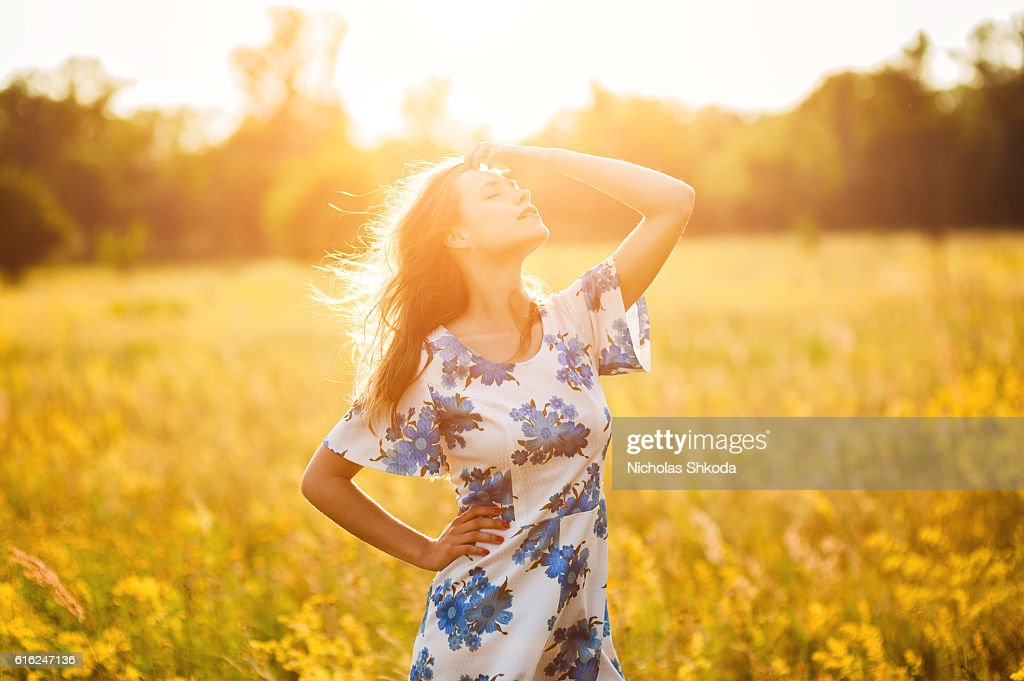 Beautiful girl the flowers field woman the flowers field sunset : Stock Photo