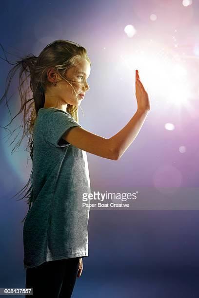 Beautiful girl touching warm light beam