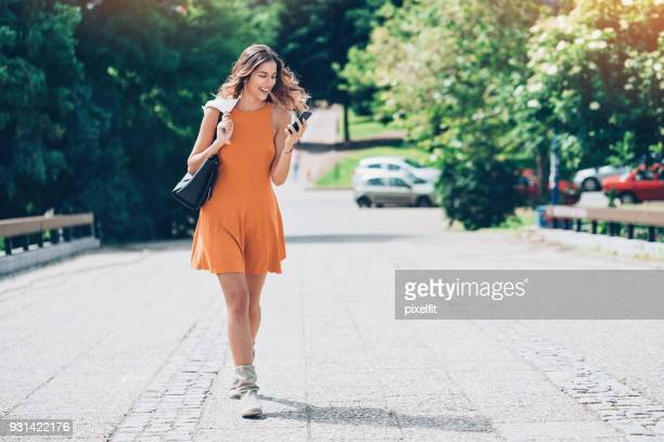 beautiful girl walking and texting outdoors - girl power stock photos and pictures