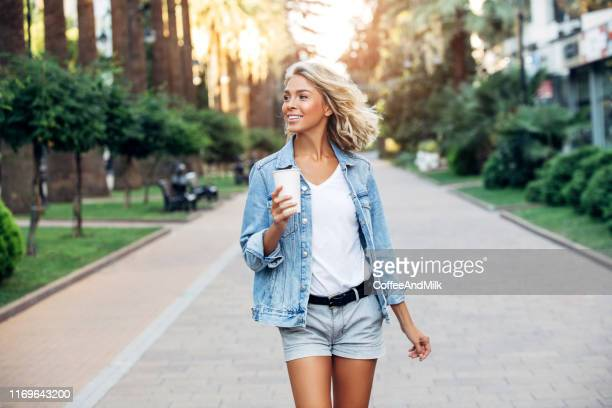 beautiful girl walking on the street with cup of coffee - shorts stock pictures, royalty-free photos & images