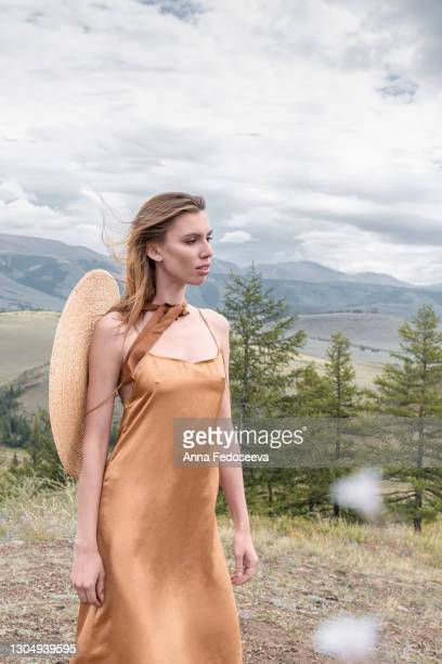 a beautiful girl walks in the mountains. majestic nature. gold-colored dress and straw hat. tourist trip. - long dress stock pictures, royalty-free photos & images