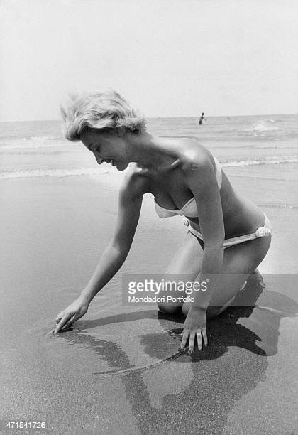 A beautiful girl wearing a white bikini drawing a circle with her finger on the wet sand of the shoreline crouched on the sand and mirrored on the...
