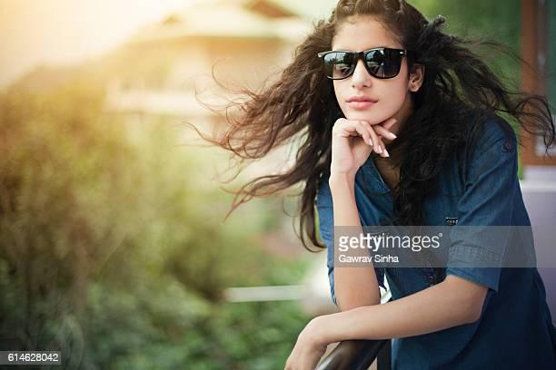 Beautiful girl wearing sunglasses enjoying fresh air in balcony.