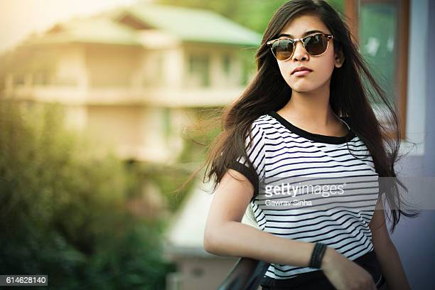 Beautiful girl wearing sunglasses enjoying fresh air in balcony.