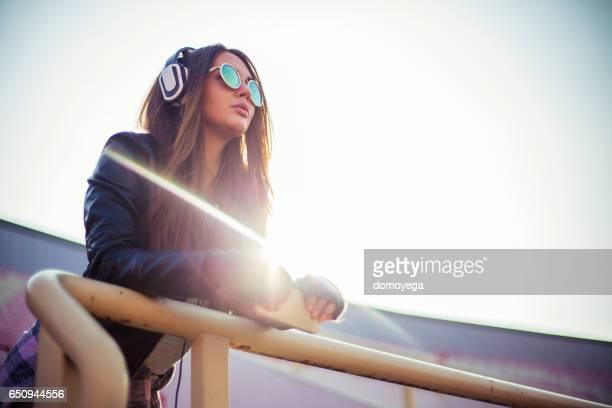 Schönes Mädchen mit einem Kopfhörer und Smartphone auf der Tribüne