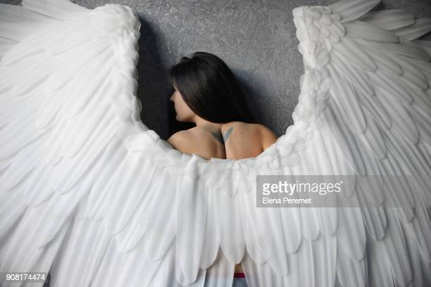 Beautiful girl with angel wings seen from behind looking to the side