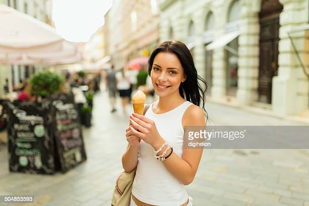 Beautiful girl with gelato on the street of summer city