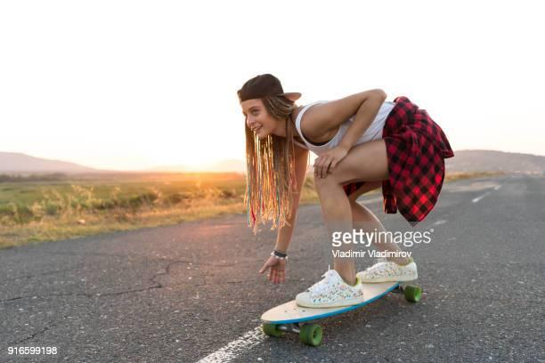 Belle fille avec longboard patinage sur route