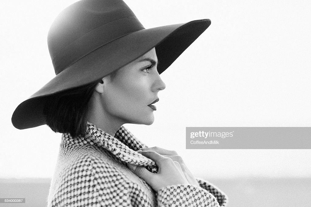 Schönes Mädchen mit make-up, das in klassischer Mantel und Mütze : Stock-Foto