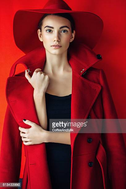 Beautiful girl with make-up wearing red coat and hat