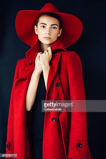 Schönes Mädchen mit Make-up in roten Mantel und Mütze