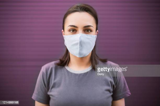 beautiful girl with medical mask to protect her from virus. corona virus pandemic - face masks imagens e fotografias de stock