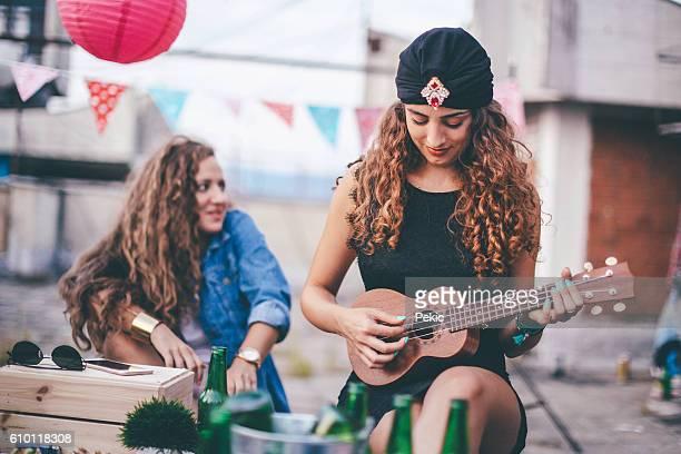 Beautiful girl with turban playing ukulele