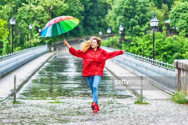 beautiful girl with umbrella dancing in the rain - umbrella stock pictures, royalty-free photos & images