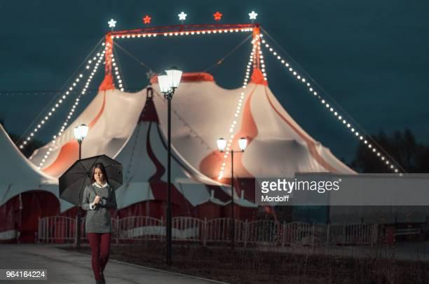 beautiful girl with umbrella is walking at night - tendone di circo foto e immagini stock