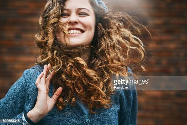 beautiful girl with winter windblown hair laughs - curly stock pictures, royalty-free photos & images