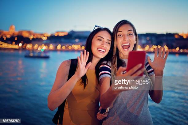 Beautiful girls are taking selfie/making video call along the river