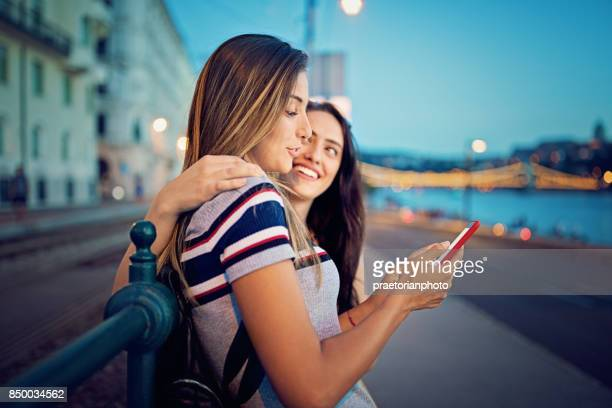 Beautiful girls are texting along the river